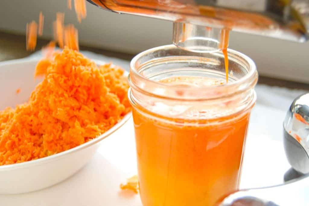 A juicer pouring out fresh carrot and orange juice.