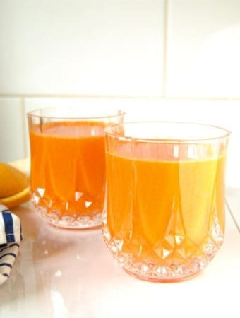 Glass of carrot orange juice on the counter.