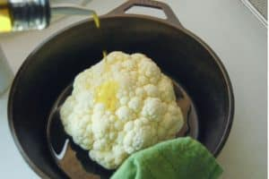 whole cauliflower head with olive oil pouring