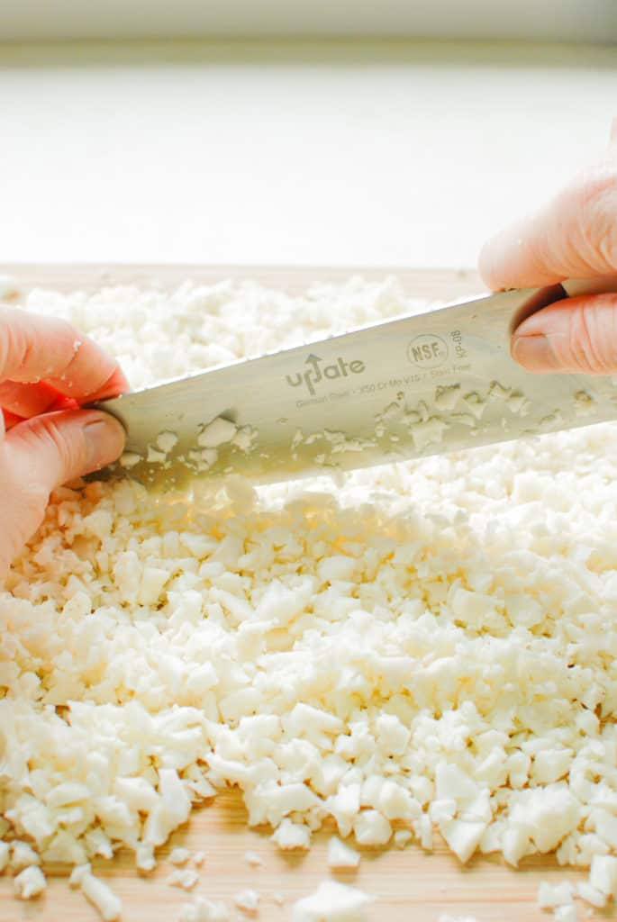 hands holding a chef's knife, cutting cauliflower into rice