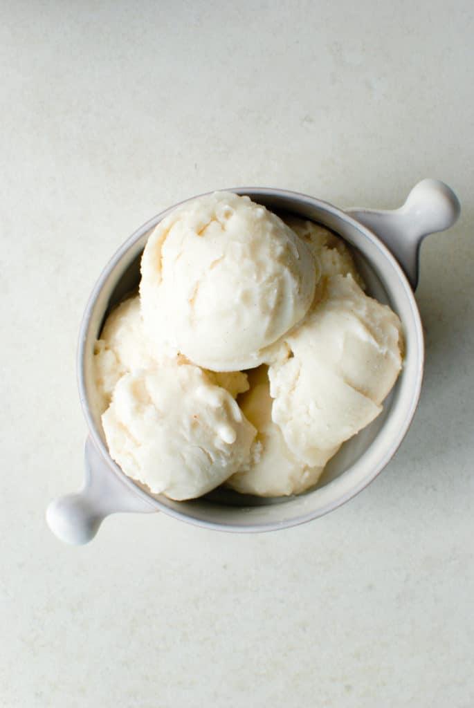 scoops of vegan vanilla ice cream in a bowl.
