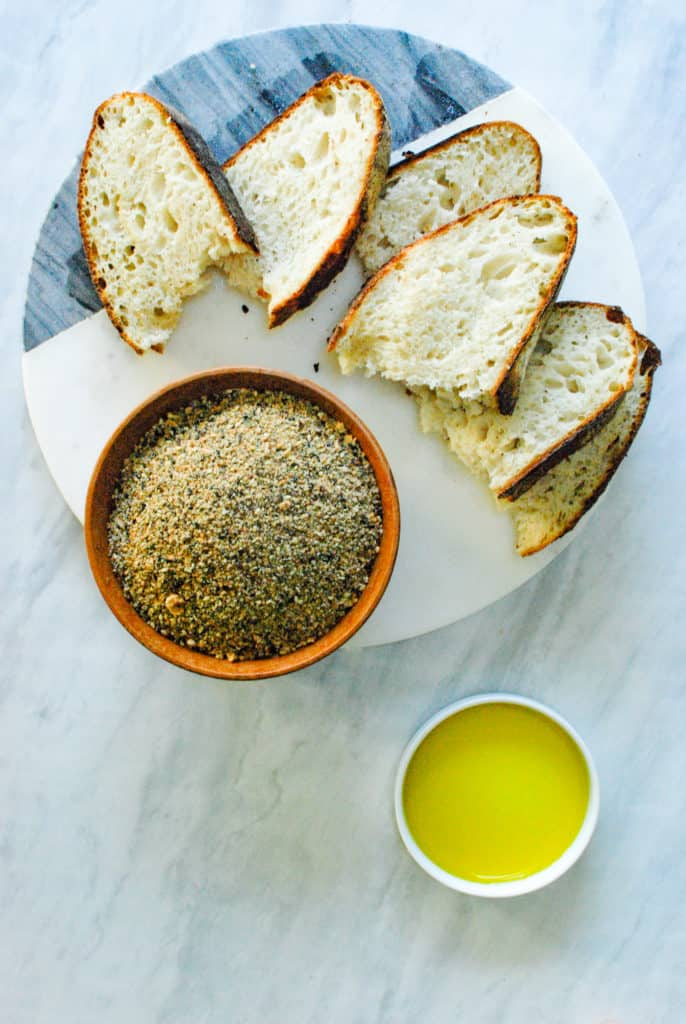 slices of bread on a marble board, with a bowl of dukkah spice, and a bowl of olive oil.