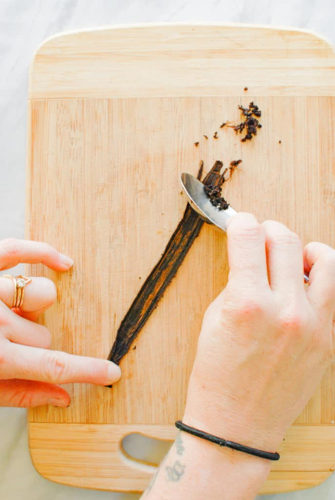 a hand scraping vanilla bean seeds from a vanilla bean pod