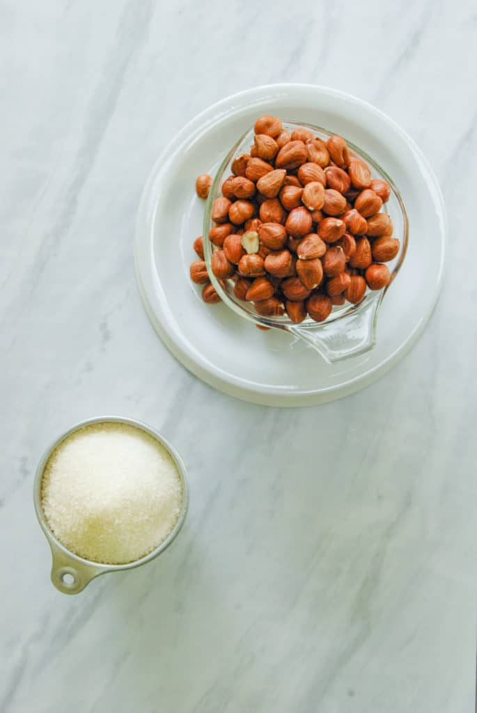 1 cup of hazelnuts and 1 cup of sugar on a counter, the ingredients for orgeat syrup.