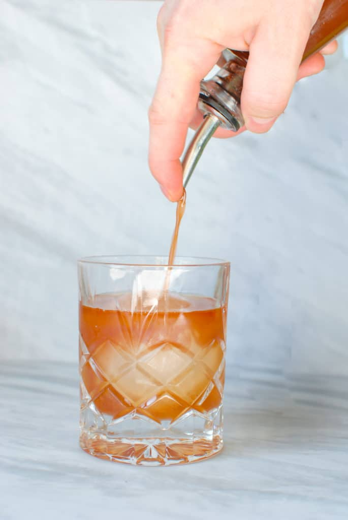a hand pouring orgeat syrup into a cocktail.