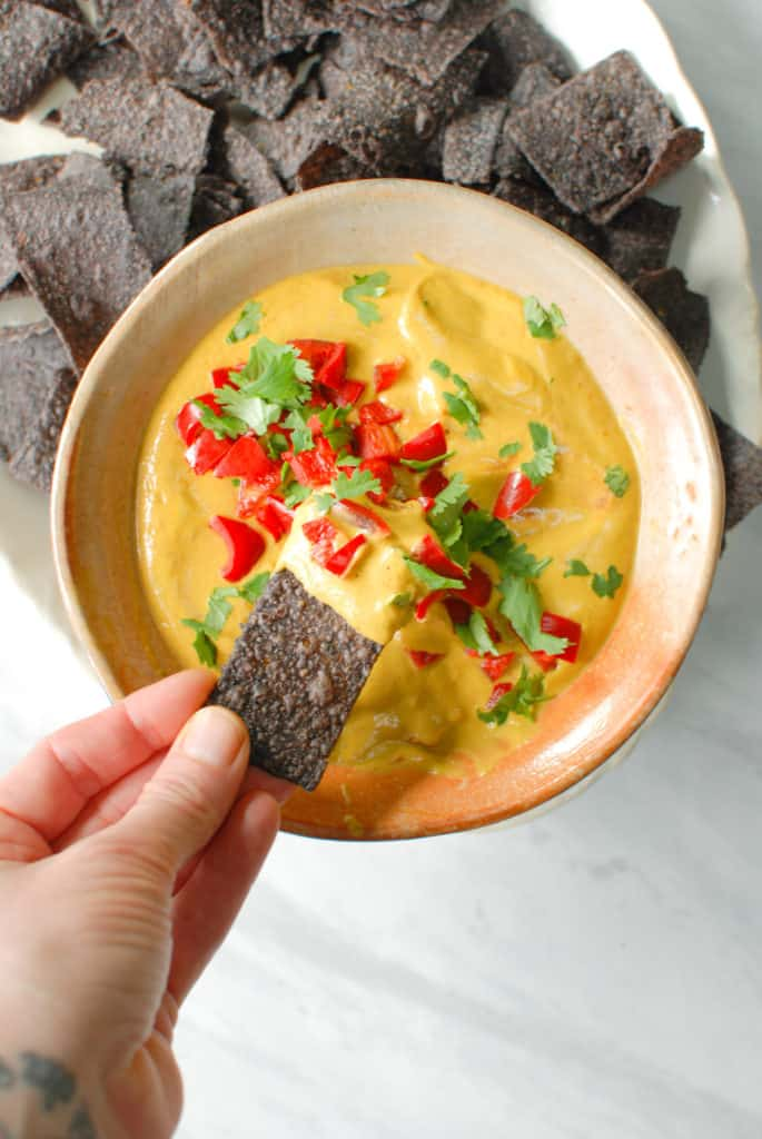 a hand dipping a chip into savory pumpkin queso