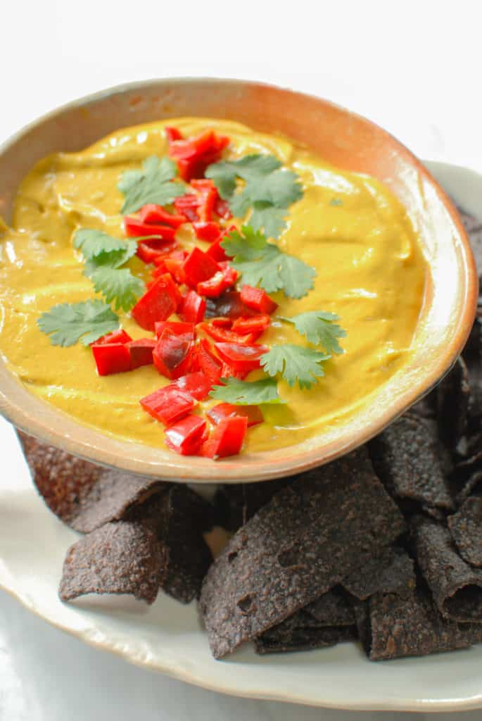a bowl of savory pumpkin dip with chips next to it.