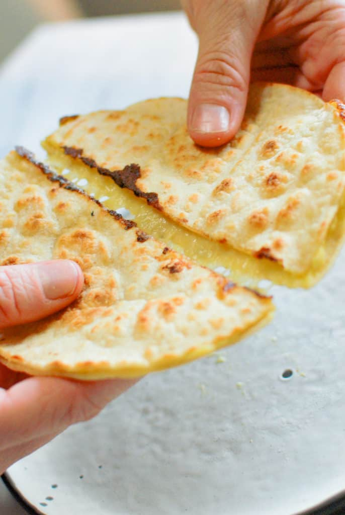 hand holding quesadilla and melty cheese pulling apart