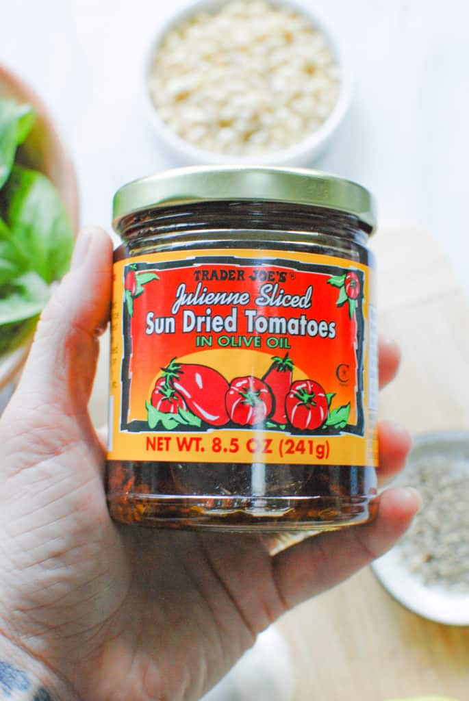 a hand holding a jar of sundried tomatoes to make pesto with