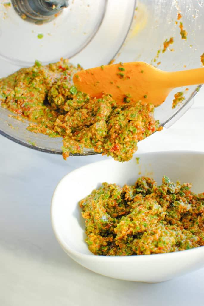 spooning sundried tomato pesto into a dish