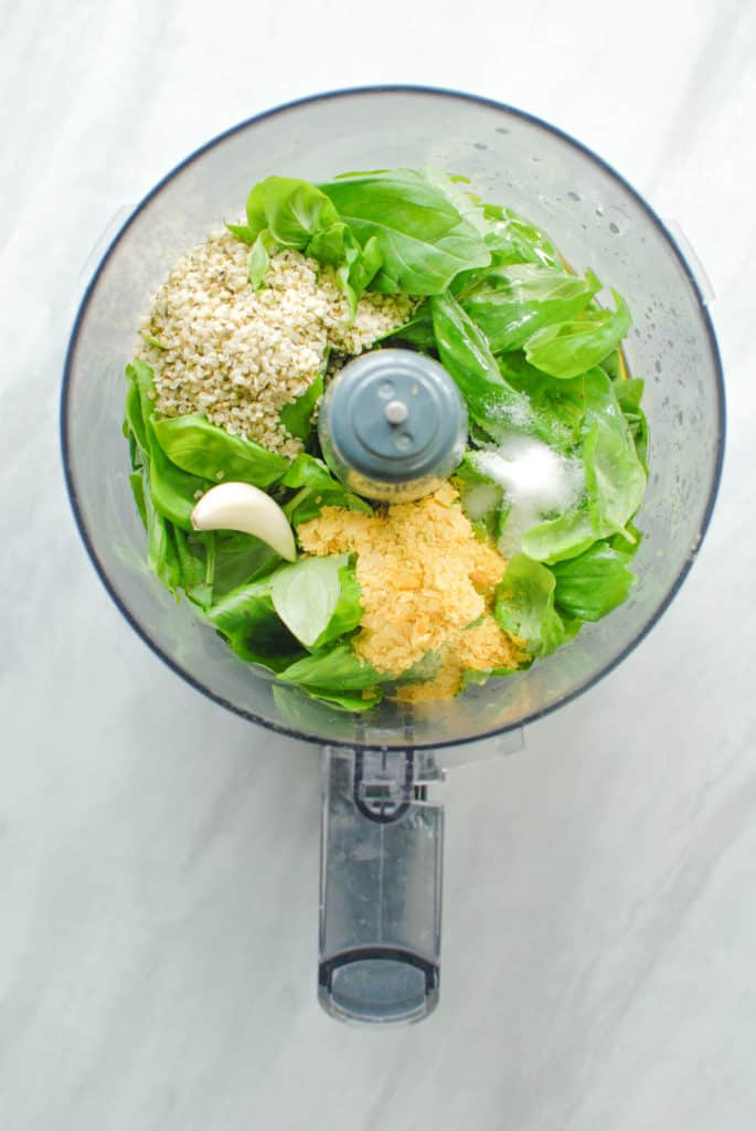 A food processor full of ingredients to make nut free pesto sauce.