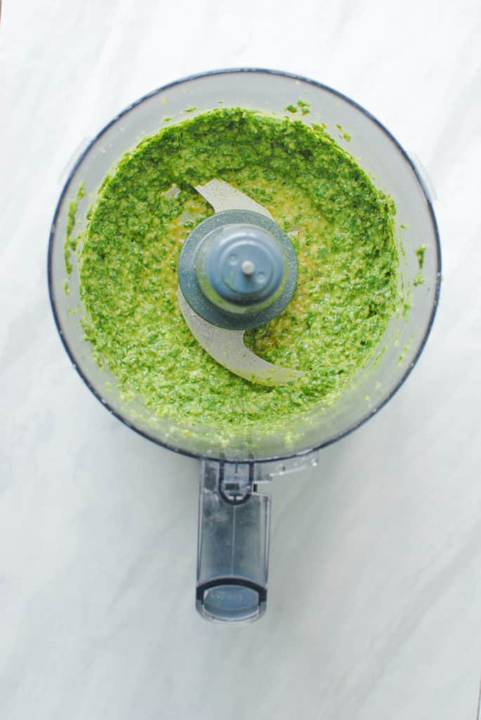 Fresh, homemade vegan nut-free pesto in a food processor.