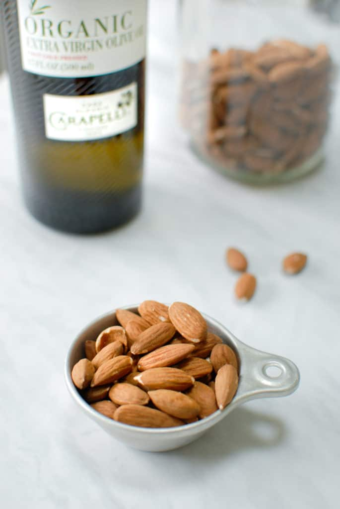 Almonds in a measuring cup to make willamette transplant's almond pesto sauce!