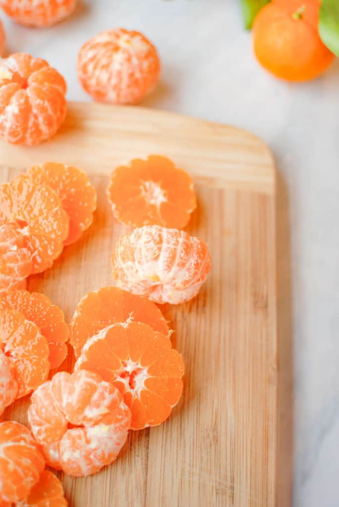 sliced clementines on a cutting board, to use in a clementine upside down cake.