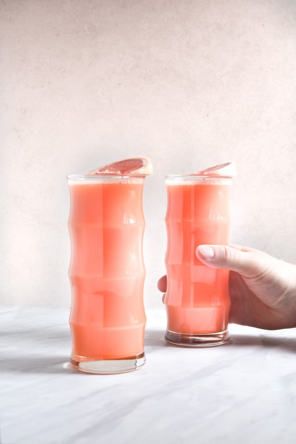 hand reaching for a glass of grapefruit juice