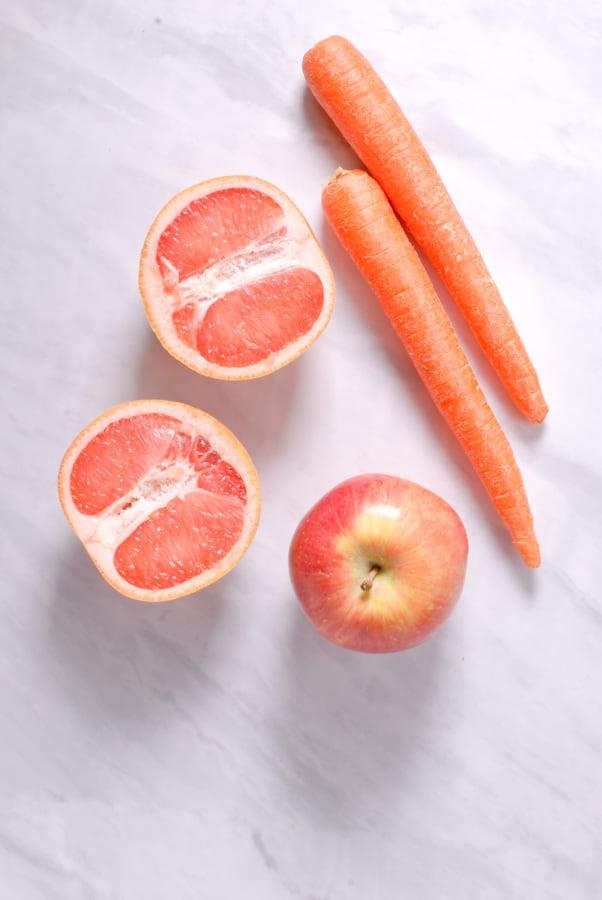 an apple, 2 carrots, and a grapefruit