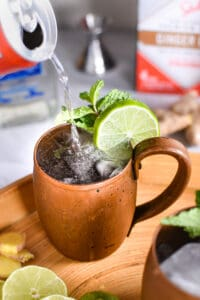 pouring ginger beer into a mexican mule drink