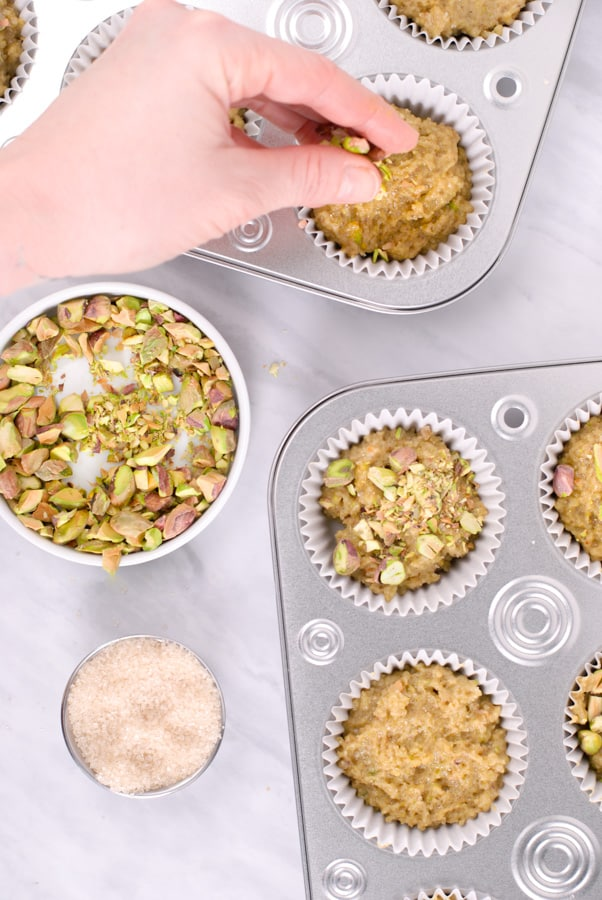hand sprinkling chopped pistachios on top of muffins