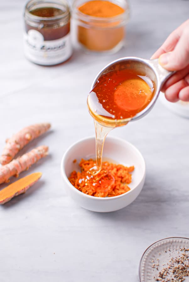 pouring honey over minced fresh turmeric root