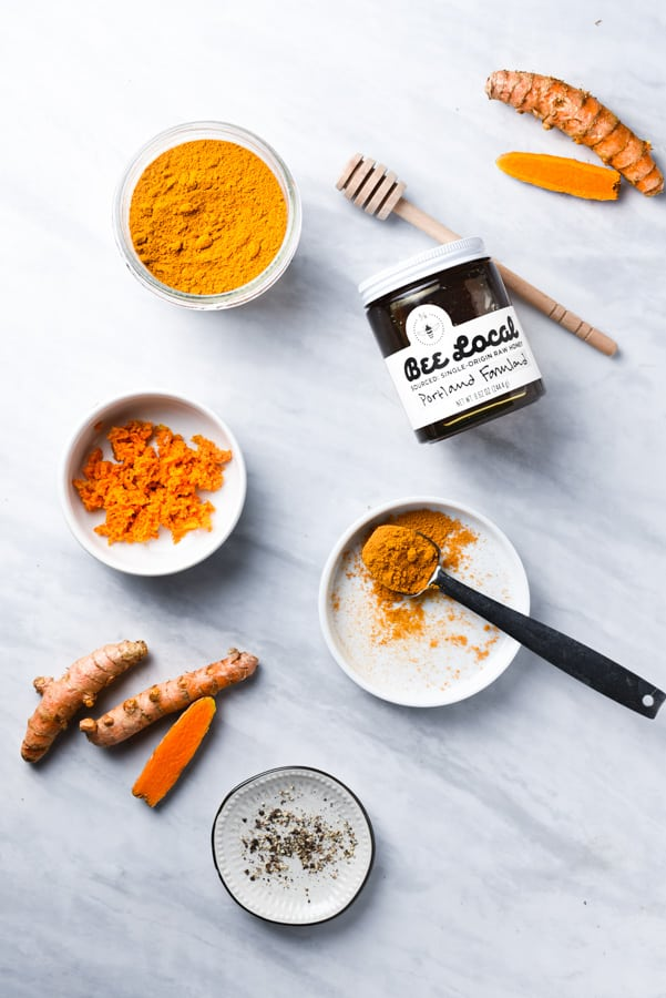 powdered turmeric, fresh turmeric, and honey on a counter