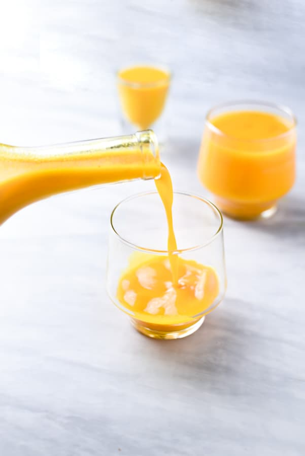 Pouring fresh turmeric juice into a glass