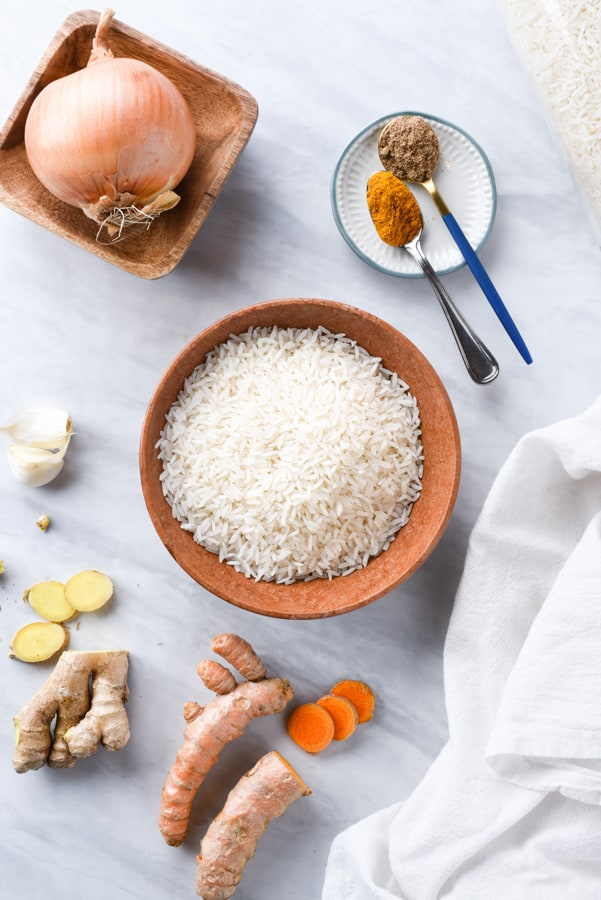 all the ingredient to make turmeric rice on a marble board