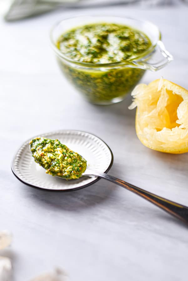 a spoon overflowing with parsley pesto
