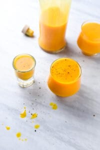fresh turmeric juice shots on a marble counter
