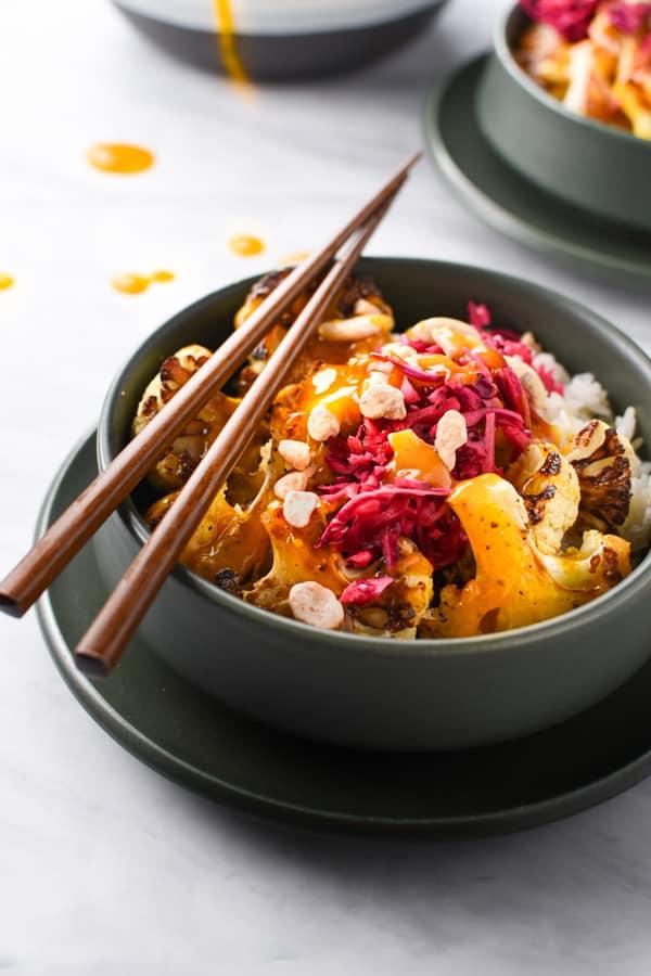 Chopsticks resting on a rice bowl with orange turmeric sauce