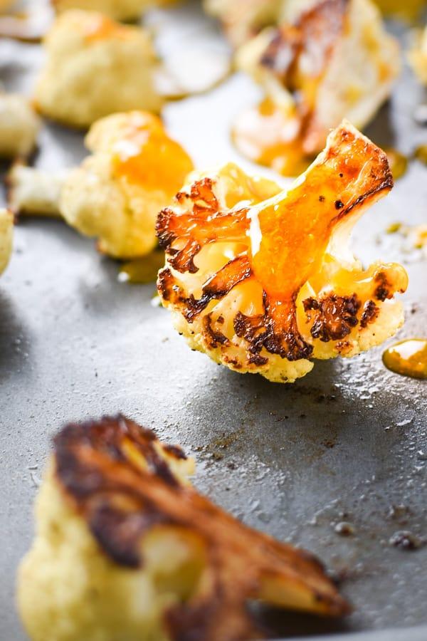Close up of orange sauce dripping over cauliflower pieces
