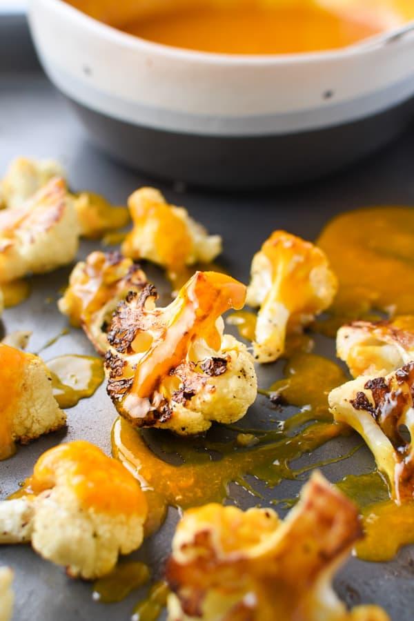 Roasted cauliflower drizzled with orange turmeric sauce on a sheet pan