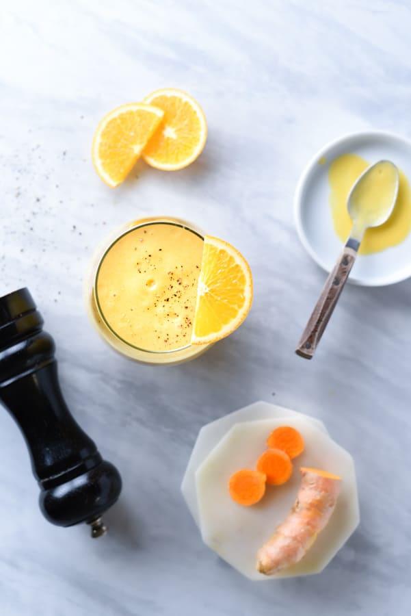 Overshot of orange peels and a turmeric mango smoothie