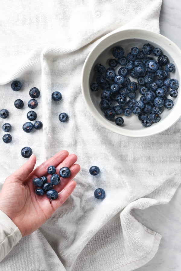 a hand placing wet blueberries onto a kitchen towel