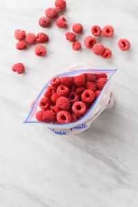 close up on a plastic bag full of frozen raspberries