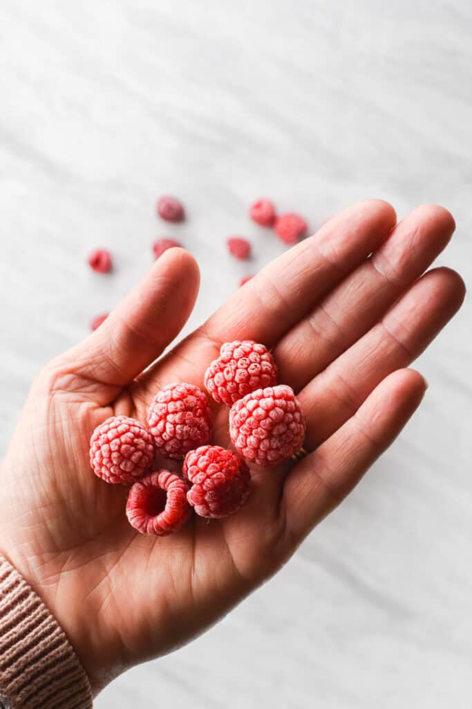 a hand holding frozen raspberries with a layer of frost on them