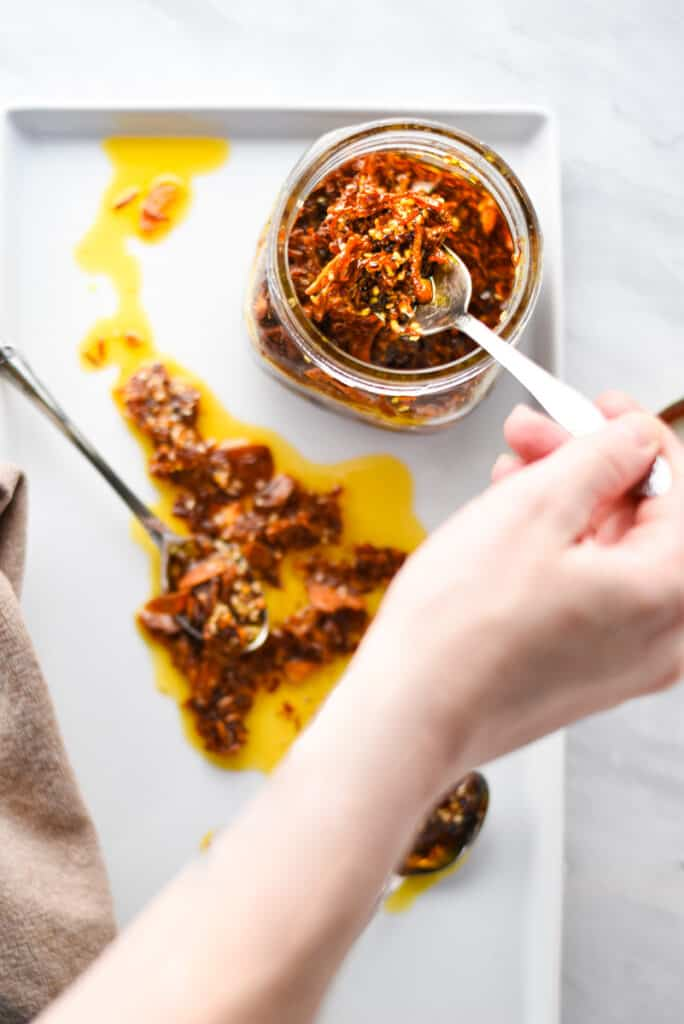 A hand spooning spicy chili crisp out of a jar