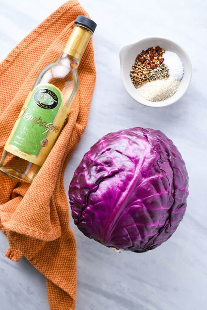 A head of purple cabbage, bottle of vinegar, and blend of spices on the counter.