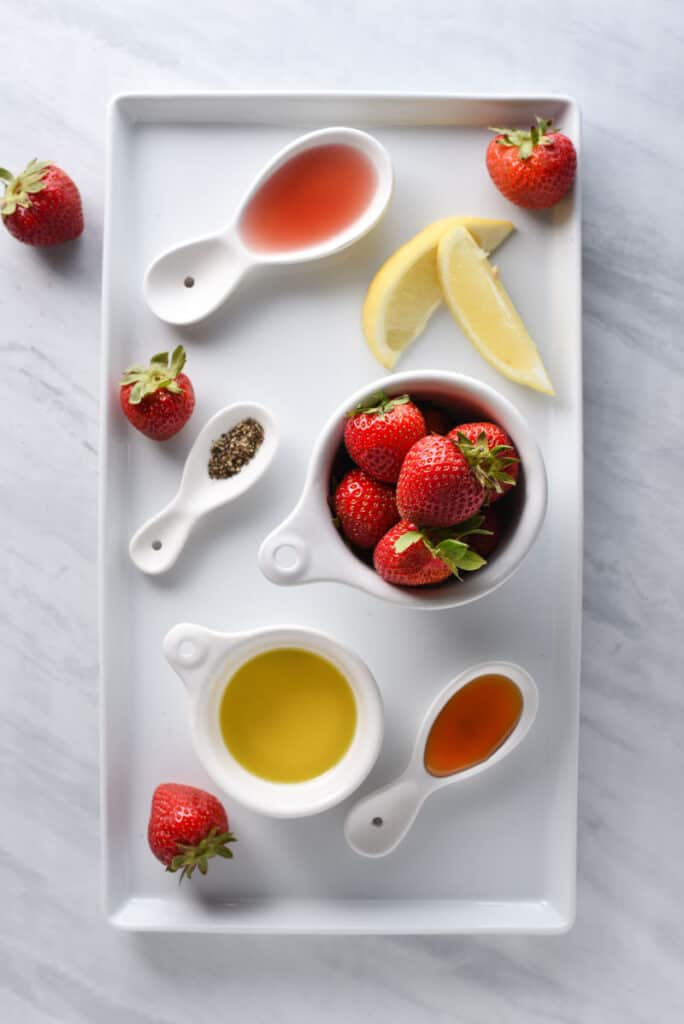 Ingredients to make strawberry salad dressing on a tray.