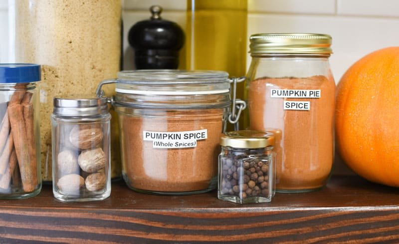 Jars of homemade pumpkin pie spice on a kitchen shelf.
