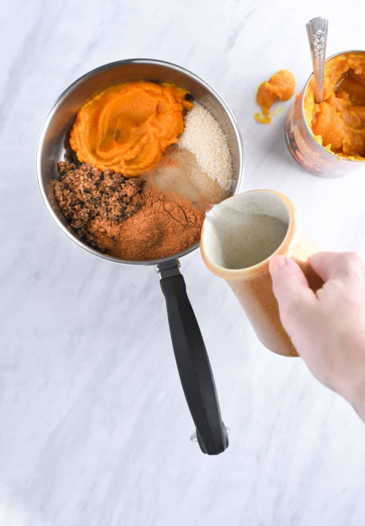 A hand pouring pumpkin spice syrup ingredients into a pot.