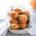 Vegan pumpkin muffins in a towel on the counter.