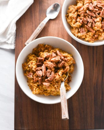 two bowls of pumpkin oatmeal on the table.