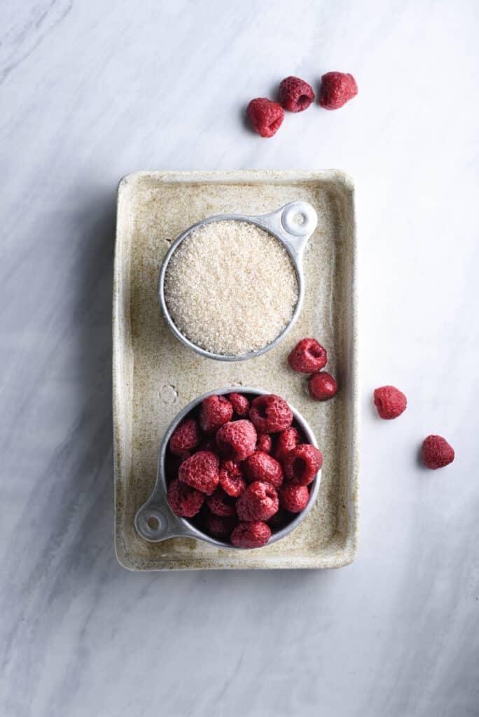 Fresh raspberries and cane sugar in bowls.
